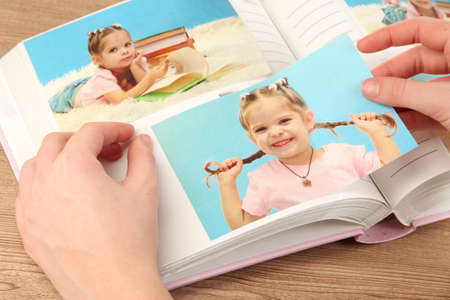 photo: Photos in hands and photo album on wooden table