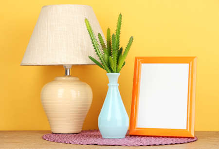 Colorful photo frame, lamp and flowers on wooden table on yellow background photo