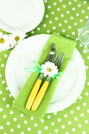 Knife and fork wrapped in napkin, on plate, on color tablecloth  background photo