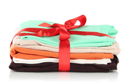 Pile of clothing with red ribbon and bow isolated on white photo