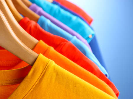 Lots of T-shirts on hangers on blue background photo