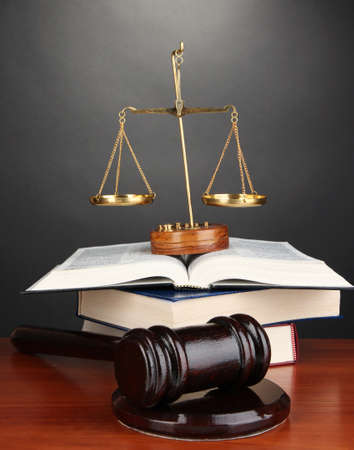 judicial proceeding: Wooden gavel, golden scales of justice  and books on grey background Stock Photo