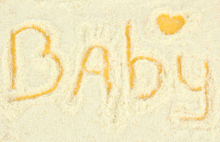 Word baby making with powdered milk on yellow background photo