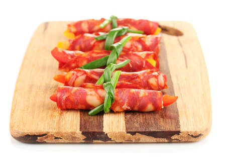 Salami rolls on wooden board, isolated on white photo