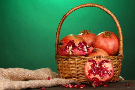 Ripe pomegranates on basket on wooden table on green background photo