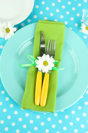 Knife and fork wrapped in napkin, on plate, on color tablecloth  background Stock Photo - 19127647