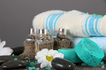Oil spa towels on bamboo mat on gray background photo