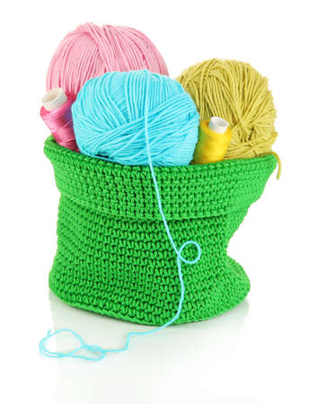 crochet: Colorful yarn for knitting in green basket isolated on white