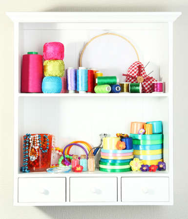 Beautiful white shelves with thread and material for handicrafts photo