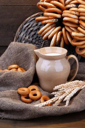 boublik: jar of milk, tasty bagels and spikelets on wooden background