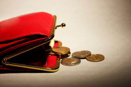 economise: female red wallet with coins on grey background