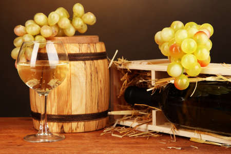 Wooden case with wine bottle, barrel, wineglass and grape on wooden table on brown background Stock Photo - 19173211