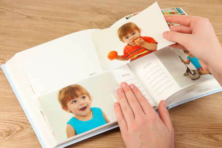 Photos in hands and photo album on wooden table Stock Photo - 19361352
