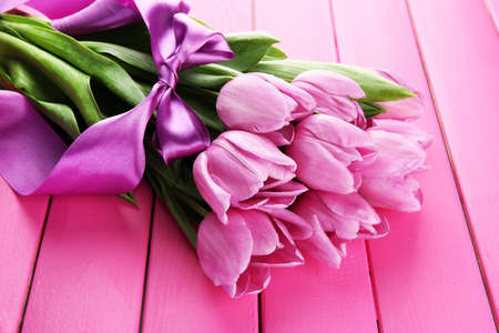 Beautiful bouquet of purple tulips on pink wooden background photo
