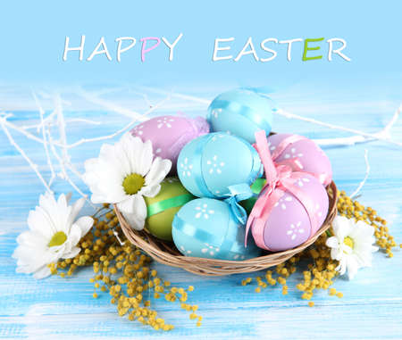 Easter eggs in basket and mimosa flowers, on blue wooden background photo