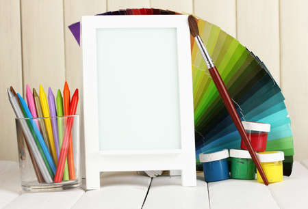 Photo frame as easel with artists tools on wooden background