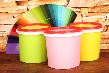Paint pots, palette of colors on wooden table on stone wall background photo