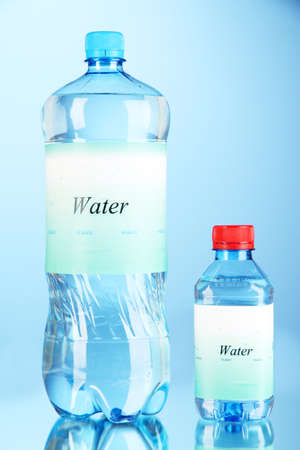 Different water bottles with label on blue background photo