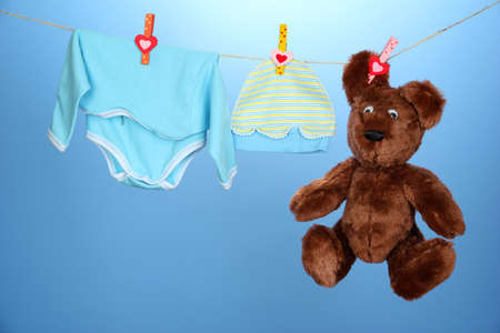 Baby clothes hanging on clothesline, on blue background photo