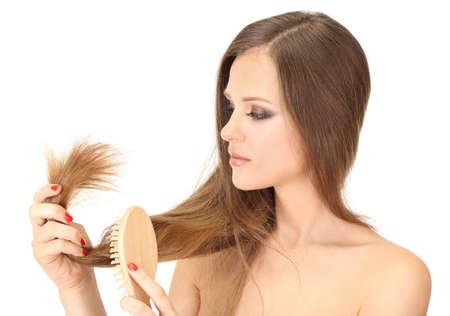 peigne: Belle femme tenant les pointes fourchues de ses longs cheveux, isol� sur blanc