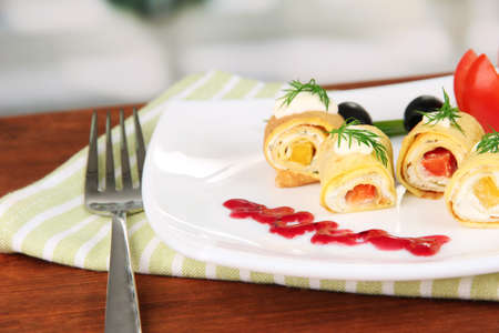 Egg rolls with cheese cream and paprika,on plate, on bright background photo