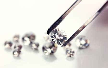 Beautiful shining crystal (diamond) in the tweezers, isolated on white photo