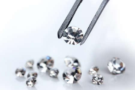 Beautiful shining crystal (diamond) in the tweezers, isolated on white