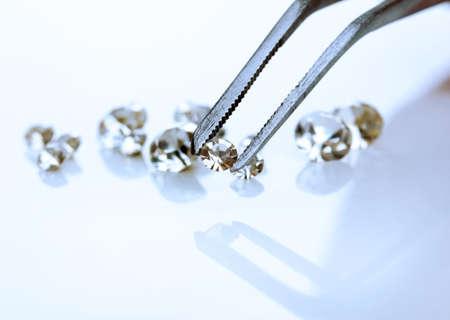 pinzas: Hermoso cristal brillante (diamante) en las pinzas, aislado en blanco Foto de archivo