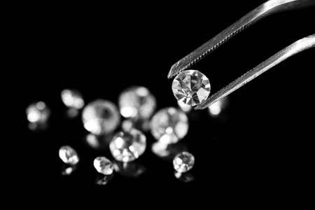 pinzas: Hermoso cristal brillante (diamante) en las pinzas, sobre fondo negro
