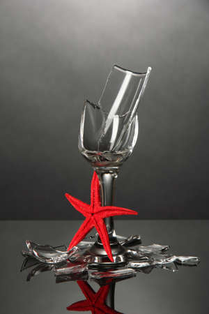 Broken wineglass with sea star on grey background photo