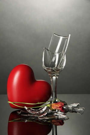 Broken wineglass and heart on grey background photo