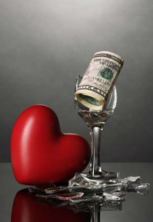 Broken wineglass, heart and money on grey background photo