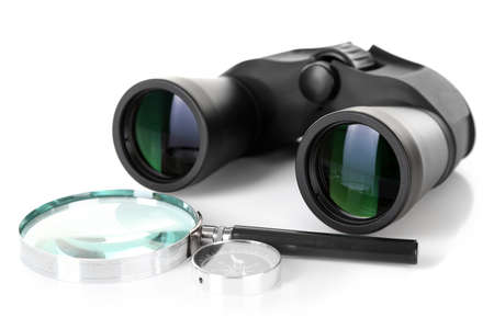 Black modern binoculars with magnifying glass and compass isolated on white photo