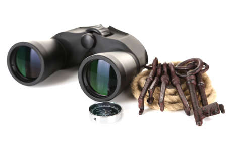 Black modern binoculars with rope, old keys and compass isolated on white photo