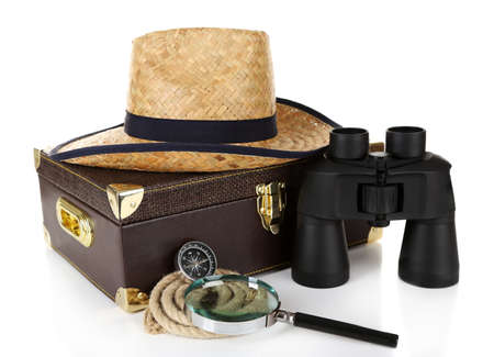 Black modern binoculars with suitcase and straw hat isolated on white photo
