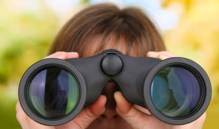 Black modern binoculars in hands on green background photo