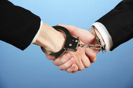 law breaking: Man and woman hands and breaking handcuffs on color background Stock Photo
