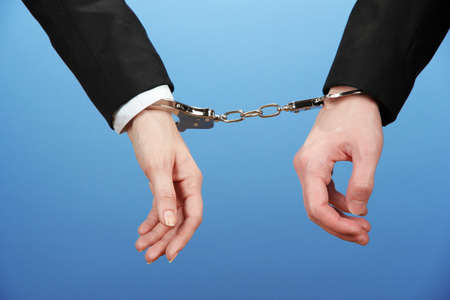manacles: Man and woman hands and breaking handcuffs on color background Stock Photo