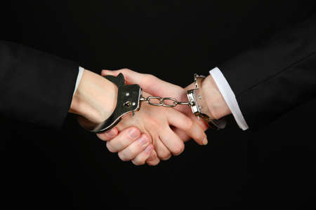 Man and woman hands and breaking handcuffs isolated on black background Stock Photo - 19227333