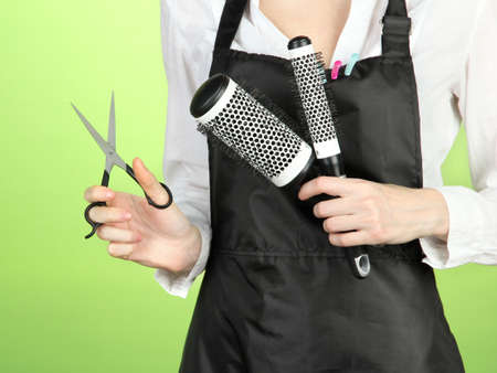 Hairdresser in uniform with working tools, on color background photo
