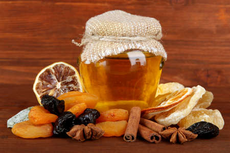 Jar of honey and dried fruits on wooden background photo