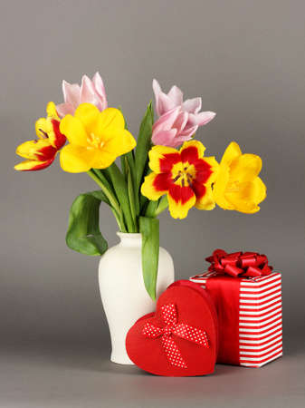 Beautiful tulips in bucket with gifts on grey background photo