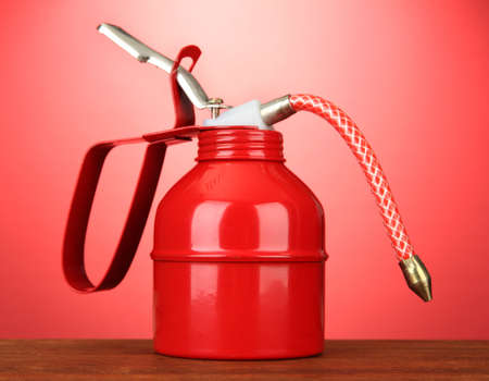 Oil can on red background photo