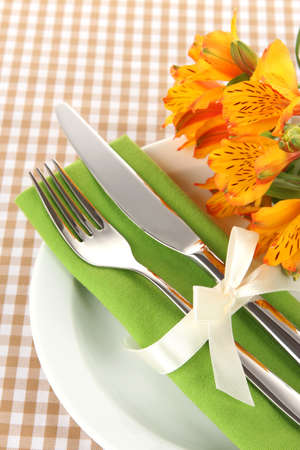 Festive dining table setting with flowers on checkered background photo