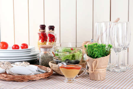 Table setting on checkered tablecloth on wooden background photo