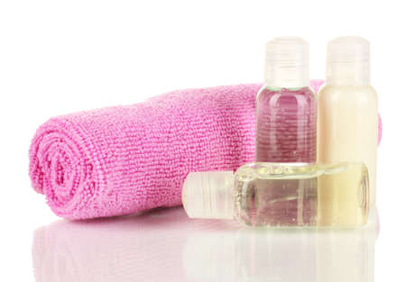 Hotel cosmetic bottles with towel isolated on white photo
