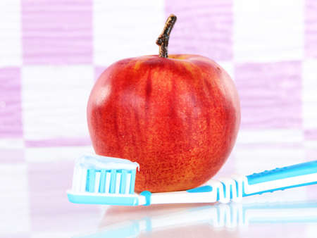 Apple with a toothbrush on shelf in bathroom photo