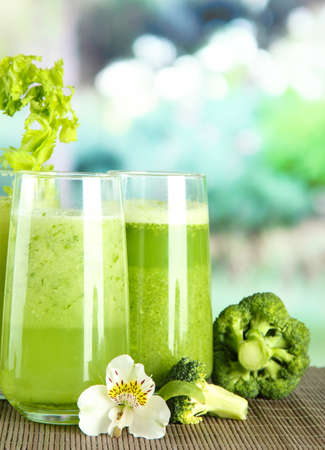 juice fresh vegetables: Glasses of vegetable juice, on bamboo mat, on green background