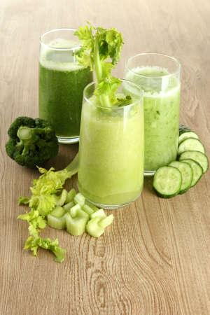 Bicchieri di succo di verdura verde su sfondo di legno