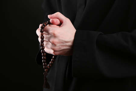 Priest holding rosary, on black background photo